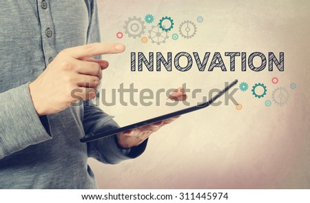 Young man pointing at Innovation text with colorful gears over a tablet computer - stock photo