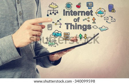 Young man pointing at Internet of Things concept over a tablet computer - stock photo