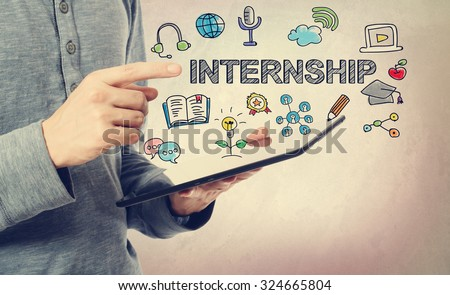 Young man pointing at Internship concept over a tablet computer - stock photo