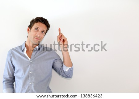 Young man pointing at message on white background