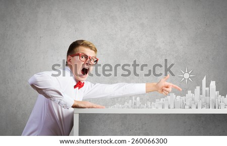 Young man pointing at modern city model - stock photo