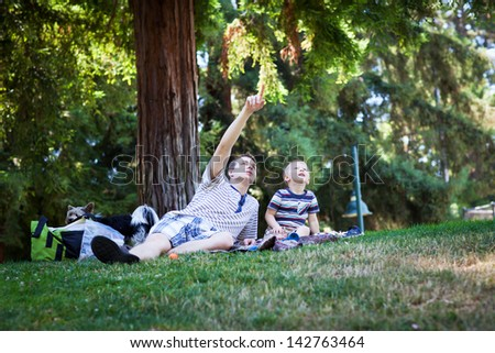 Young man pointing at something in the sky - stock photo