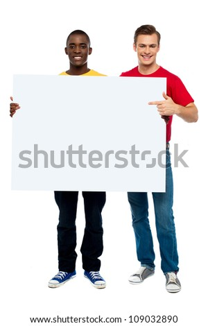 Young man pointing at white ad board while other holding board