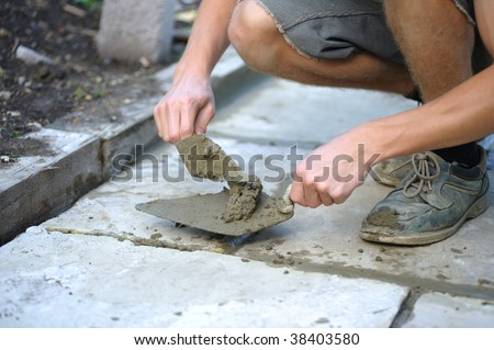 Young man pointing paving slabs - stock photo