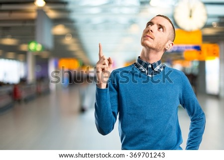 Young man pointing up on unfocused background