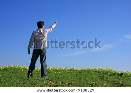 Young man pointing with his finger to the blue sky - stock photo
