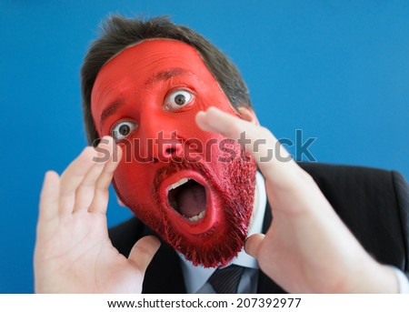 Young man portait with red painted face and copy space