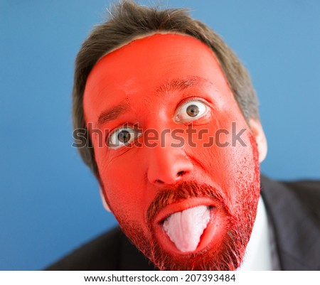 Young man portait with red painted face and copy space - stock photo