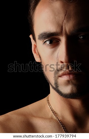 Young man portrait half face with scar on black background - stock photo