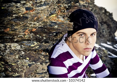 Young man portrait in casual clothing on the rocks - stock photo