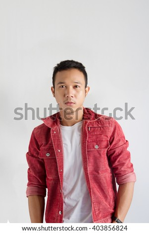 young man portrait in white shirt and red jacket  on gray background