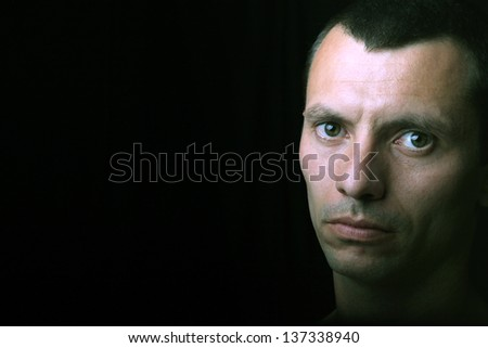 young man portrait, on a black background - stock photo
