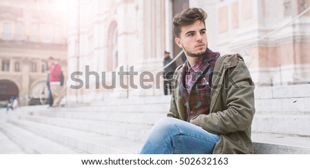 Young man portrait sit on the stairs in front of San Petronio Cathedral in the city center of Bologna, Italy. Concept of urban lifestyle.