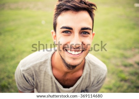 Young man portrait while smiling at the park - stock photo