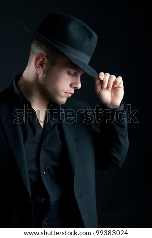 Young man portrait with hat on black background.