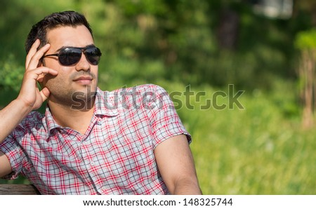 Young man posing and wearing sunglasses, outdoor