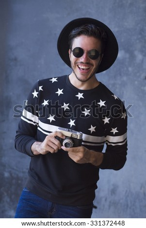 Young man posing with a trendy outfit with a vintage camera in a urban background - stock photo