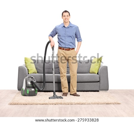 Young man posing with a vacuum cleaner in front of a modern gray sofa isolated on white background - stock photo