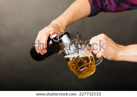 young man pouring beer from bottle into a mug glass