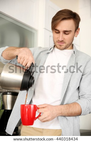 Young man pouring coffee into cup in kitchen