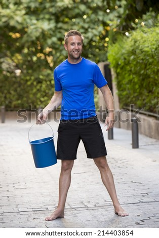 young man pouring ice water bucket on his head getting wet outdoors in internet viral media network challenge campaign to support degenerative sclerosis and neuronal disease and disorder  - stock photo