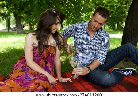 Young man pouring white wine in wineglass - stock photo