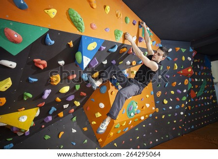 Young man practicing bouldering in indoor climbing gym - stock photo