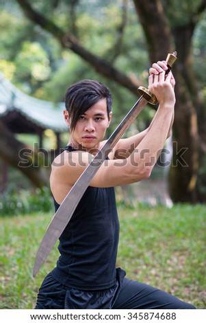 Young man practicing kung fu with sword in a park in Hong Kong. Filtered image. - stock photo