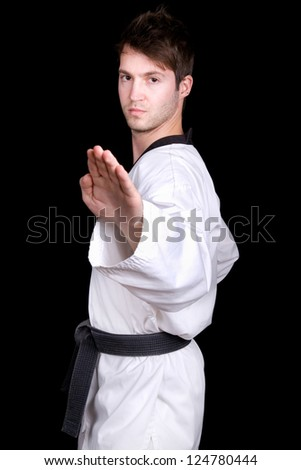 Young man practicing martial arts over black background - stock photo