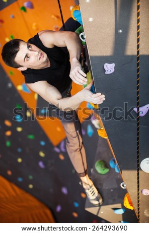 Young man practicing top rope climbing in indoor climbing gym, hands in focus - stock photo