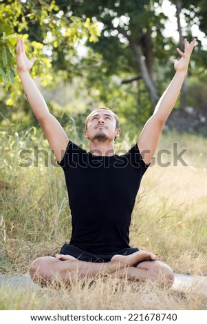 Young man practicing yoga and meditating - stock photo