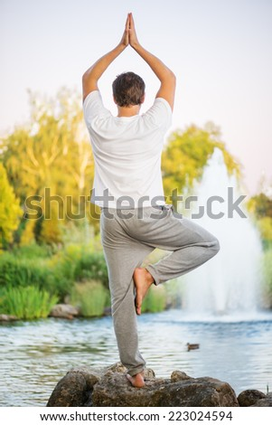 Young man practicing yoga, doing tree pose and turning back upon cmera. With a beautiful green scenery of park on background - stock photo