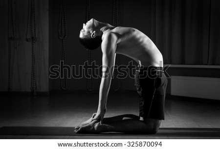 young man practicing yoga in the gym - stock photo
