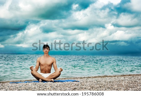 Young Man Practicing Yoga near the Sea. Healthy Lifestyle Concept. Copy Space.  - stock photo