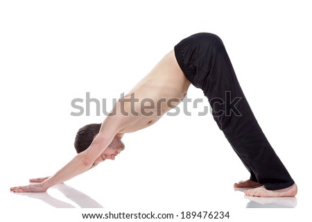 young man practicing yoga on white background, standing in the Downward Facing Dog position. - stock photo
