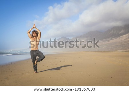 young man practicing yoga tree pose on the beach