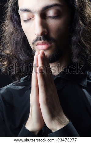 Young man praying in darkness