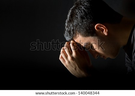 Young man praying in the dark - stock photo