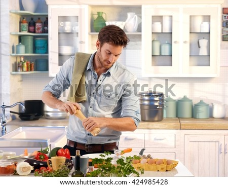 Young man preparing food at home in kitchen using pepper-mill.