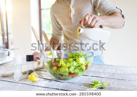 Young man preparing healthy vegetable salad - stock photo