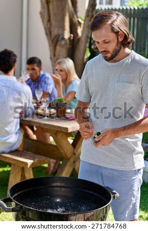 young man preparing to start fire for friends outdoor barbecue garden party - stock photo