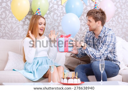 Young Man Presenting A Birthday Gift To His Girl Friend Looking Amused Sitting On Couch