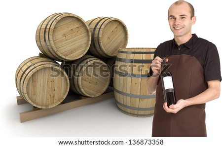 Young man presenting a wine bottle, with barrels at the background - stock photo