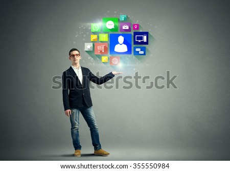 Young man presenting in hand social networking icons on color background