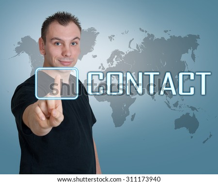 Young man press digital Contact button on interface in front of him - stock photo