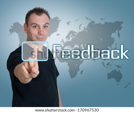 Young man press digital Feedback button on interface in front of him - stock photo
