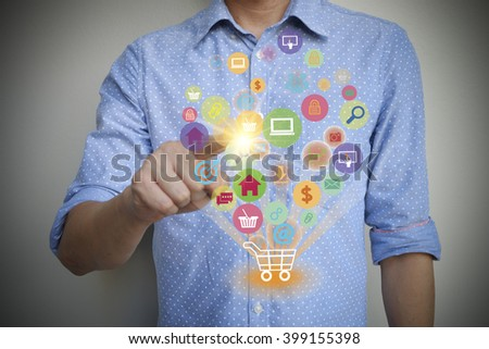 young man press shopping cart with application software icons , business concept,  shopping online concept , business idea - stock photo