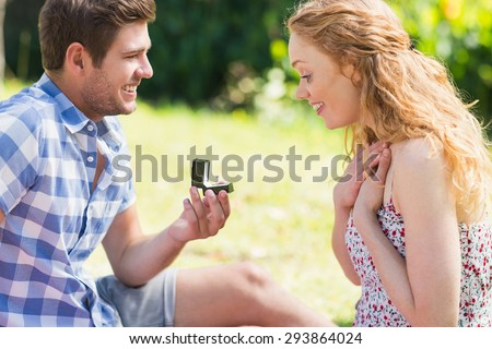 Young man propose to girlfriend on a sunny day - stock photo