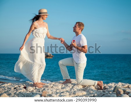 Young man proposing marriage to happy young woman, sea background - stock photo