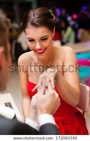 young man proposing with an engagement ring to his love in a restaurant - stock photo